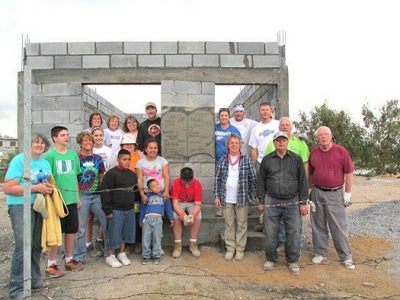 A team and a family in front of their new house in Mexico