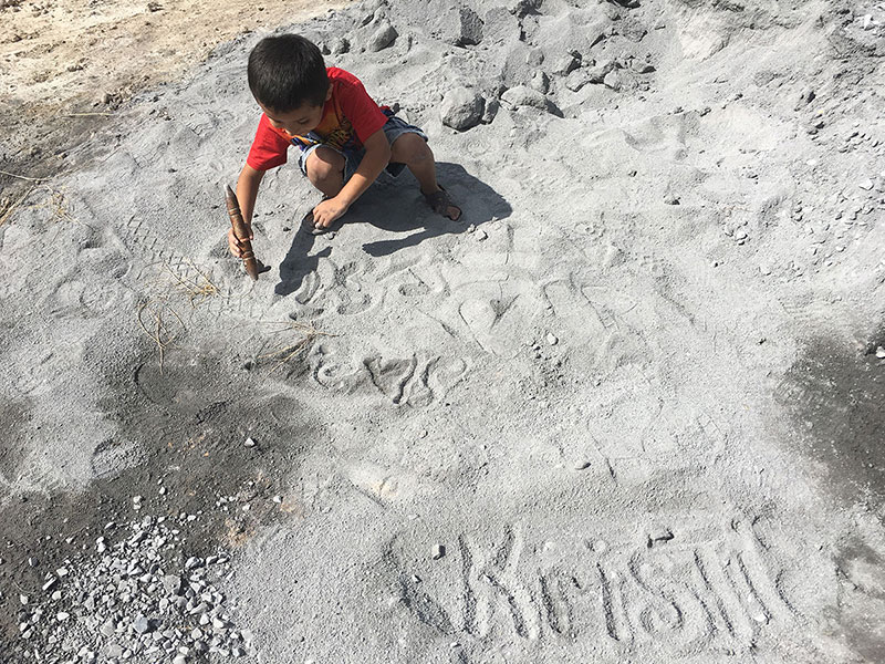 A little boy writing in the sand on the jobsite in Reynosa