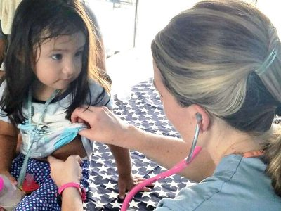 A medical volunteer from the US treating a kids at our medical clinic